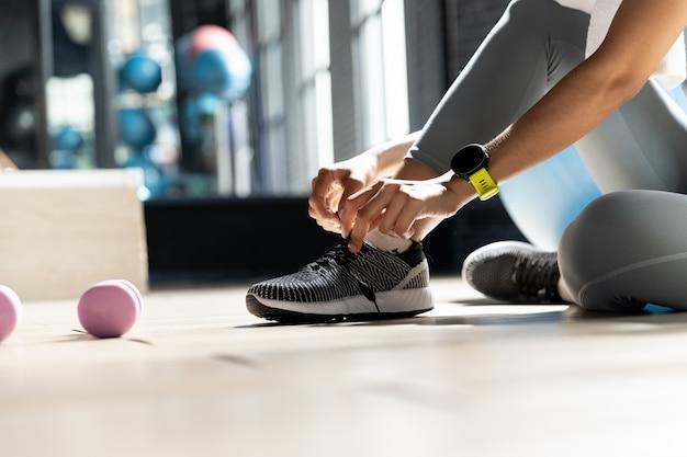 Le mani della donna che legano le scarpe preparatevi a fare esercizio in palestra