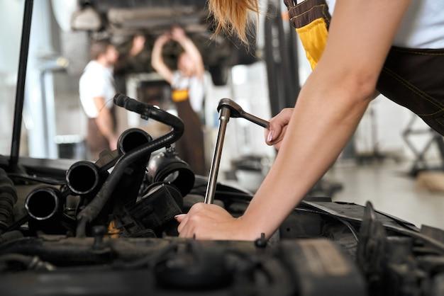 Le mani della donna che riparano automobile sotto il cappuccio con lo strumento.