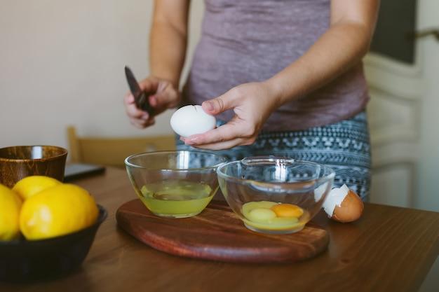 Le mani della donna che rompono un uovo intero in una ciotola.