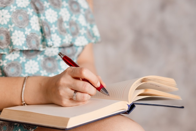 Le mani della donna che scrivono informazioni utili nel blocco note. la mano della ragazza con una penna rossa scrive il compito nel taccuino. scrivere le informazioni sulle pagine del taccuino facendo i compiti. lista di controllo