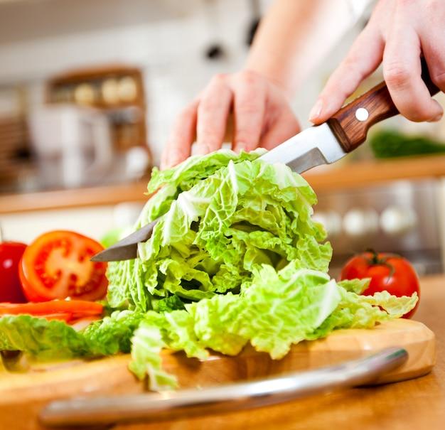 Le mani della donna che tagliano lattuga, dietro gli ortaggi freschi.