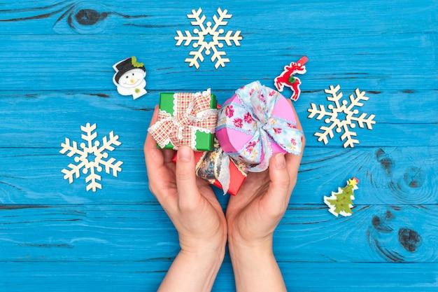 Le mani della donna che tengono i contenitori di regalo di natale vicino ai fiocchi di neve e agli ornamenti di legno del nuovo anno sulla vecchia tavola blu