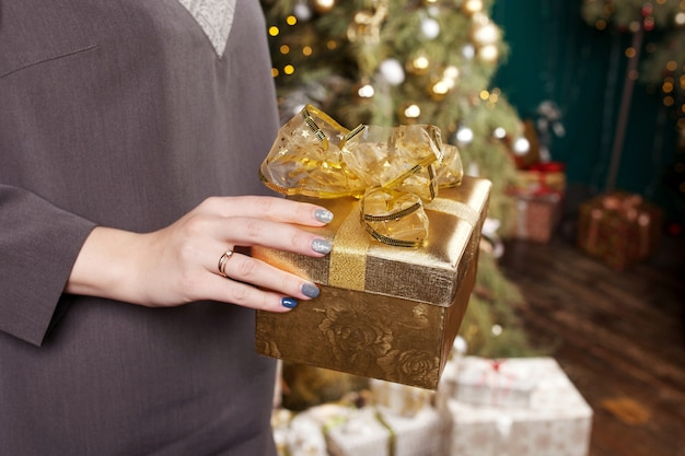 Le mani della donna che tengono il contenitore di regalo dell'oro. natale, anno nuovo, compleanno.
