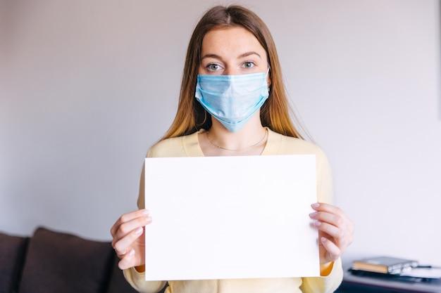 Le mani della donna che tengono il libro bianco dimensioni a4, fuoco selettivo. indossando maschera da virus
