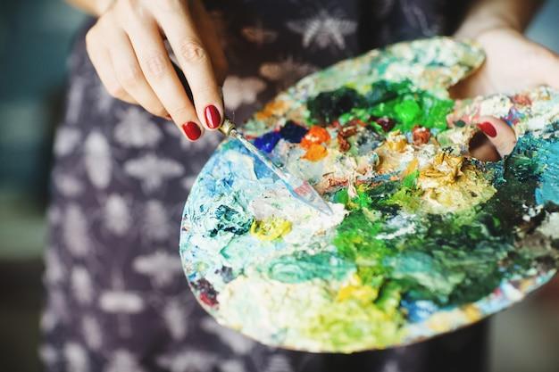 Le mani della donna che tengono il pennello e la tavolozza con le pitture ad olio. avvicinamento. concetto d'arte