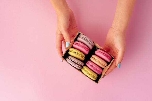 Le mani della donna che tengono scatola con i biscotti variopinti del maccherone