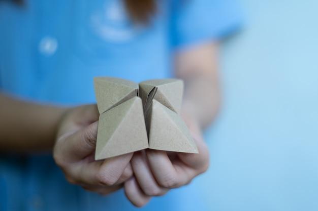 Le mani della donna che tengono un indovino di carta su fondo blu