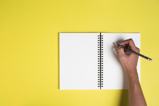 Le mani della donna con un quaderno bianco