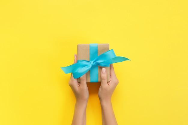 Le mani della donna danno il biglietto di s. valentino avvolto o l'altro presente fatto a mano di festa in carta con il nastro blu. scatola attuale, decorazione del regalo sulla tavola gialla, vista superiore con lo spazio della copia