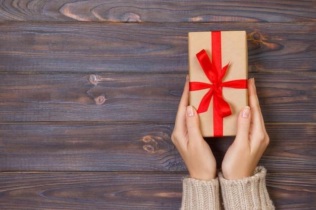 Le mani della donna danno il biglietto di s. valentino avvolto o l'altro presente fatto a mano di festa in carta con il nastro rosso. scatola attuale, decorazione del regalo sulla tavola di legno bianca, vista superiore con lo spazio della copia