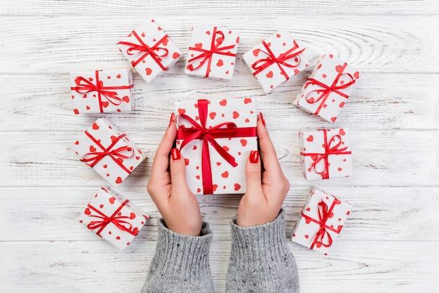 Le mani della donna danno il biglietto di s. valentino avvolto o l'altro presente fatto a mano di festa in carta con il nastro rosso. scatola attuale, decorazione rossa del cuore del regalo sulla tavola di legno, vista superiore con lo spazio della copia per voi progettazione