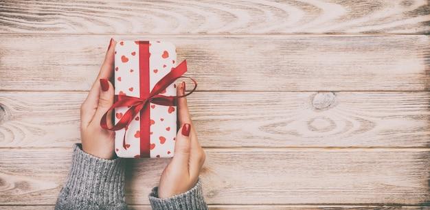 Le mani della donna danno il biglietto di s. valentino avvolto o l'altro presente fatto a mano di festa in carta con il nastro rosso.
