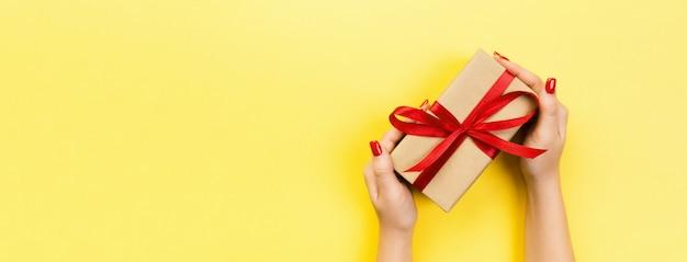 Le mani della donna danno il biglietto di s. valentino avvolto o l'altro presente fatto a mano di festa in carta con il nastro rosso