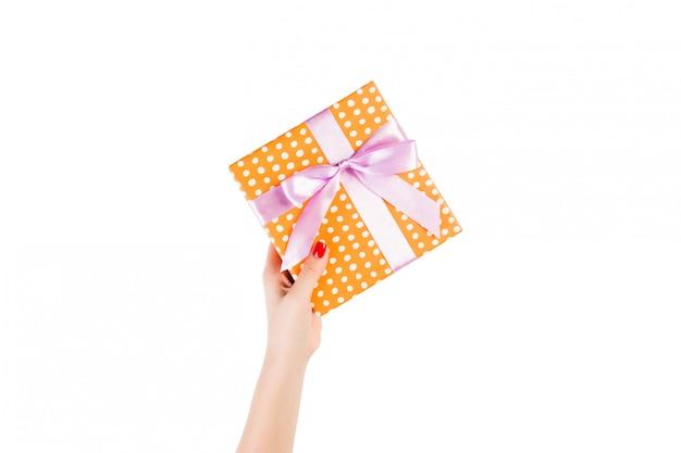 Le mani della donna danno il natale incartato o l'altro presente fatto a mano di festa in carta arancio con il nastro porpora.
