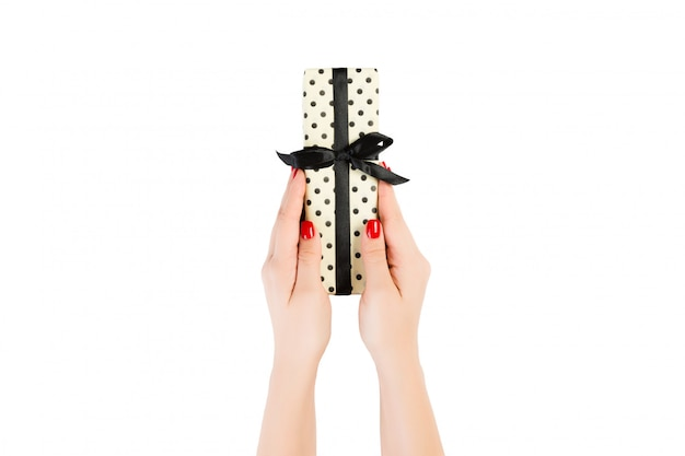 Le mani della donna danno il natale incartato o l'altro presente fatto a mano di festa in nastro nero di carta giallo. isolato su bianco, vista dall'alto. regalo di ringraziamento