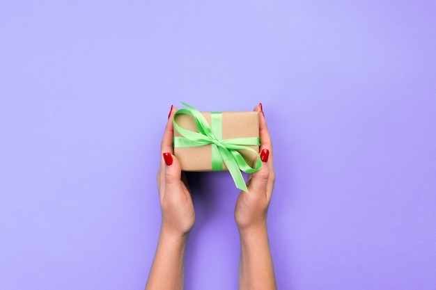 Le mani della donna danno il presente fatto a mano avvolto del biglietto di s. valentino o di altra festa in carta con il nastro verde.