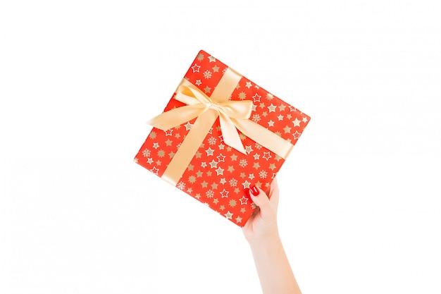 Le mani della donna danno il regalo avvolto del natale o dell'altra festa fatta a mano in carta rossa con il nastro dell'oro.
