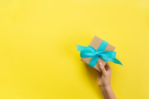 Le mani della donna danno il regalo fatto a mano di festa