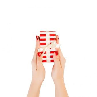 Le mani della donna danno il regalo incartato di natale o altra vacanza fatta a mano in carta rossa con nastro d'oro. isolato su bianco