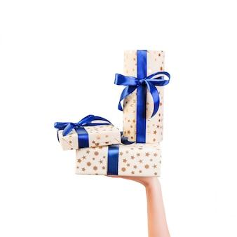 Le mani della donna danno il set avvolto di natale o di altra festa presente a mano in carta oro con nastro blu