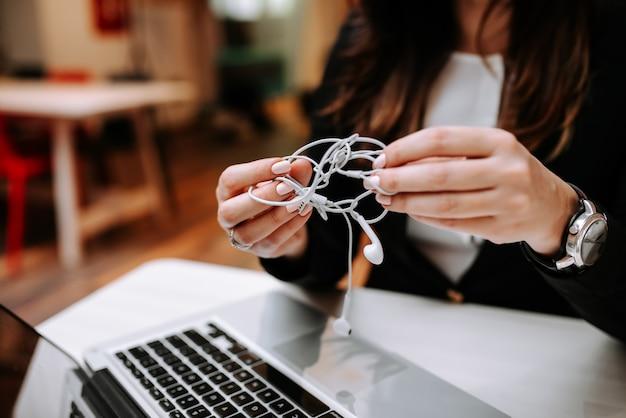 Le mani della donna di affari che provano a sciogliere le cuffie aggrovigliate. avvicinamento.