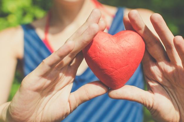 Le mani della donna di amore e di relazione che tengono cuore rosso