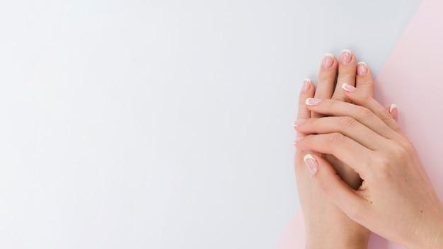 Le mani della donna di vista superiore con lo spazio della copia