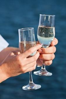 Le mani della donna e dell'uomo stanno tenendo i vetri del champagne
