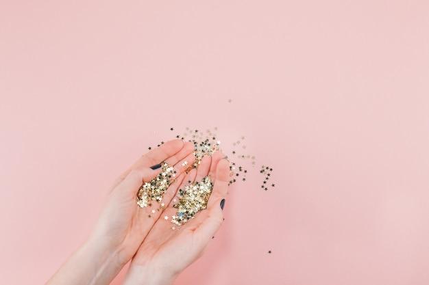 Le mani della donna hanno coperto i coriandoli dorati delle stelle sul rosa