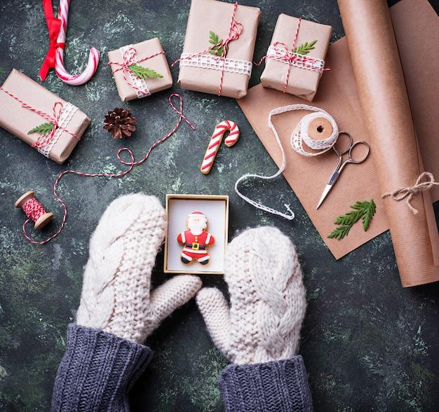 Le mani della donna in guanti che imballano le scatole con i regali dei regali di natale. vista dall'alto