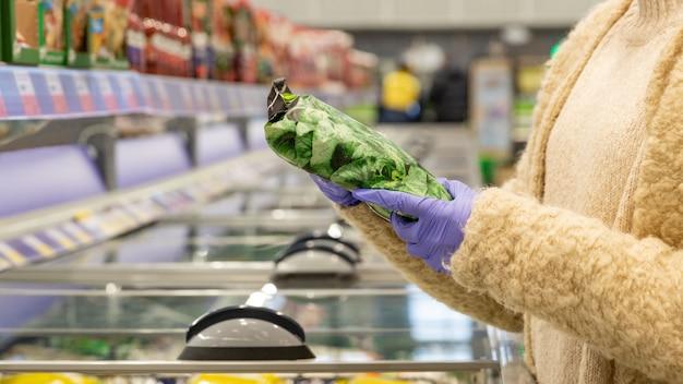 Le mani della donna in guanti medici scelgono gli spinaci surgelati nel pacchetto aprendo il congelatore in un supermercato. protettivo contro il coronavirus
