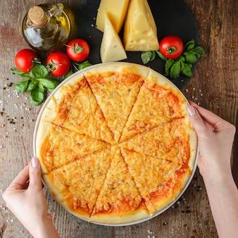 Le mani della donna prende la pizza su un piatto, vista superiore