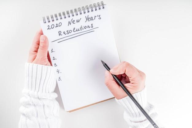 Le mani della donna scrivono gli obiettivi del nuovo anno