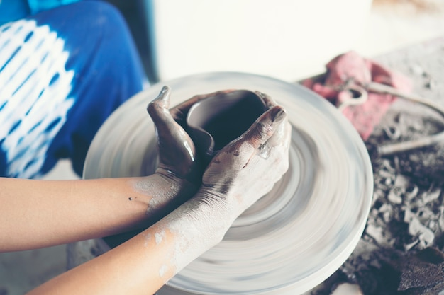 Le mani della donna si chiudono, lo studio magistrale della ceramica lavora con l'argilla su un tornio da vasaio