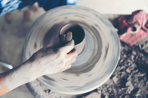 Le mani della donna si chiudono, lo studio magistrale della ceramica lavora con l'argilla