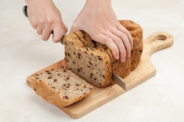 Le mani della donna stanno affettando il pane fresco da un coltello su un piano di appoggio in legno