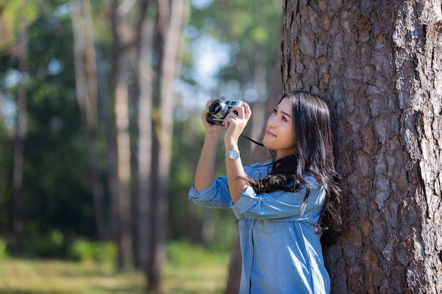 Le mani della donna tenendo la fotocamera e scattando foto nascoste nella pineta.