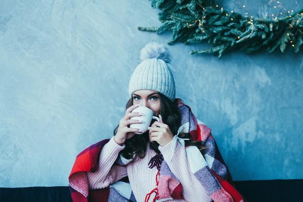 Le mani della donna tengono una tazza di caffè calda