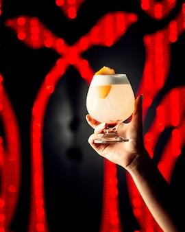 Le mani della donna tiene un bicchiere di cocktail con scorza d'arancia