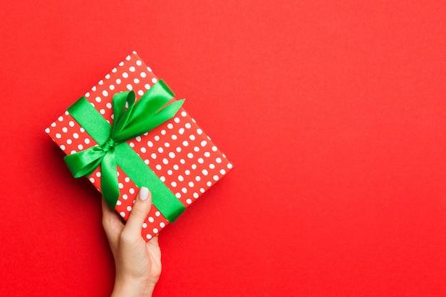 Le mani della femmina che tengono il contenitore di regalo a strisce con il nastro colorato su fondo rosso
