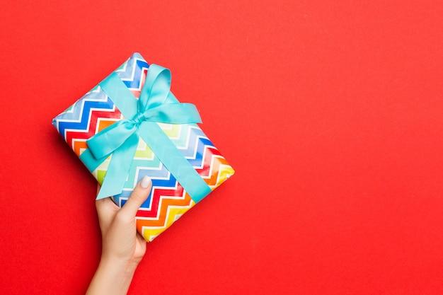 Le mani della femmina che tengono il contenitore di regalo a strisce con il nastro colorato su rosso.