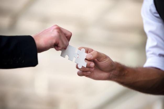 Le mani della gente di affari tengono insieme il puzzle di carta e risolvono il puzzle