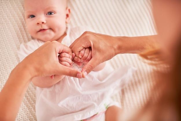Le mani della madre che tengono le mani del bambino. simbolo piegato di cuore e amore dalle dita. maternità e cura del bambino.