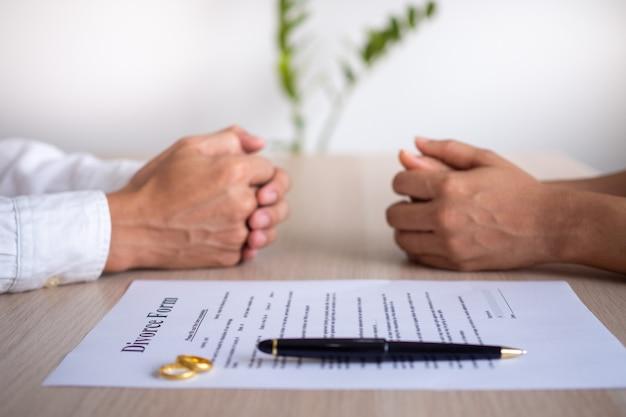 Le mani della moglie e del marito con l'ordine di divorzio, scioglimento, annullamento del matrimonio, documenti di separazione legale, limatura di divorzio o accordi prematrimoniali preparati da un avvocato.