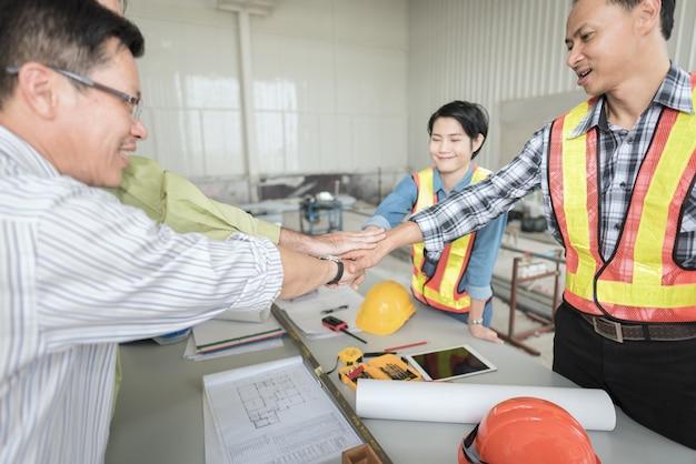 Le mani della pila di lavoro di squadra dell'ingegnere di affari si uniscono