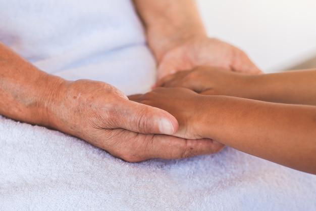 Le mani della ragazza asiatica del bambino che tengono le mani anziane del nonno si corrugano la pelle con la sensibilità e l'amore di sensibilità