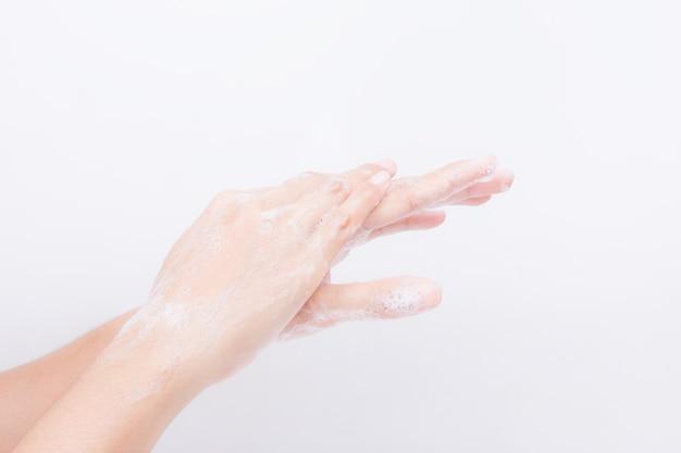 Le mani della ragazza asiatica stanno lavando con le bolle di sapone. sfondo bianco