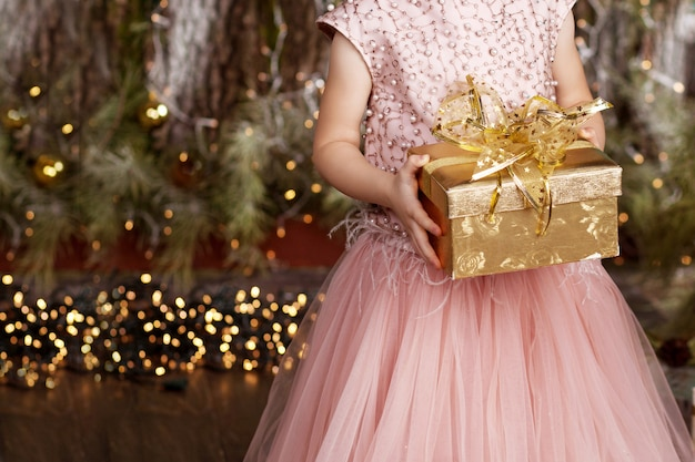 Le mani della ragazza che tengono il contenitore di regalo dell'oro. bambina con regalo di natale