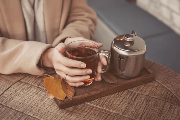Le mani della ragazza che tengono una tazza calda del primo piano del tè