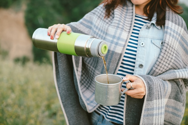 Le mani della ragazza con il thermos versa il tè caldo nella tazza sul prato sugli alberi alla mattina nebbiosa.